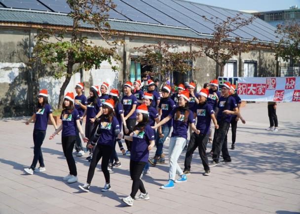 中山大學學生在高雄駁二碼頭玩快閃活動,呼籲大家在聖誕節「放下手機擁抱人群」。(中山大學圖片)